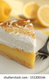 Lemon pie with meringue and a fork in a plate