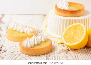 Lemon pie on the table with citrus fruits. Traditional french sweet pastry tart. Delicious, appetizing, homemade dessert with lemon curd cream. Copy space