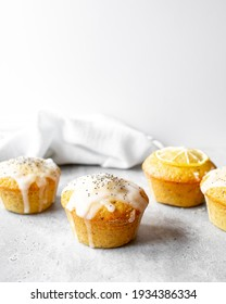 Lemon Poppy Seed Muffins on a concrete worktop and bright grey background.