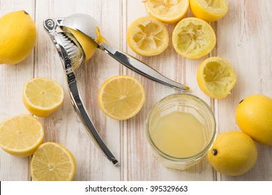 A lemon press surrounded by whole lemons, sliced lemons, squeezed lemons halves, and lemon juice in glass on a wooden surface.