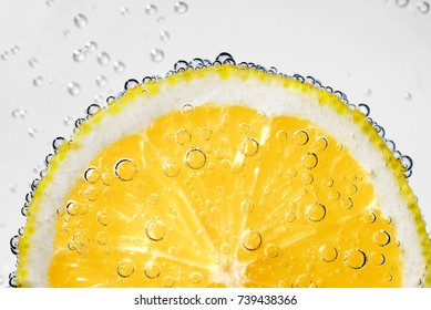 Lemon slice in carbonated soda fizz water with bubbles on white background