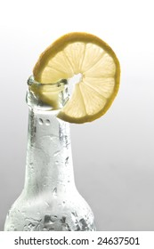 A lemon slice is decorating a bottle of corona beer. Studio shot.