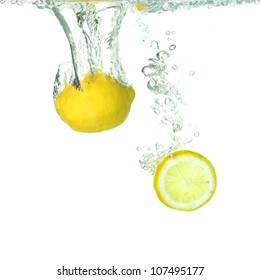 a lemon and a slice of lemon falling into clear water