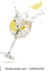 lemon slice falling into a splashing gintonic isolated on white