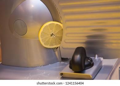 Lemon sliced on a professional slicer. Close-up.