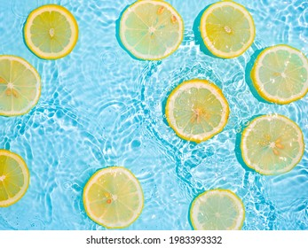 Lemon slices in clean transparent water over blue background with copy space. Water splashing on blue water surface in sunlight. Top view or flatlay. Summer, vacation, healthy eating concept