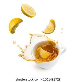 lemon slices falling into cup of tea and splashing