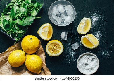 lemon and lemon slices ice salt greens on a dark surface top view