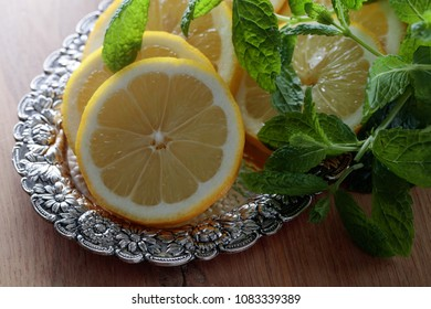 Lemon slices with mint leaves in old silver dish on a wooden table.