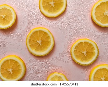 lemon slices on a light juicy pink abstract background with water drops. close up