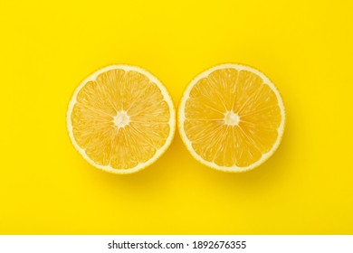 Lemon slices on a yellow minimal background. Bright juicy lemon on a yellow blank isolated background. Summer, sun, health concept.