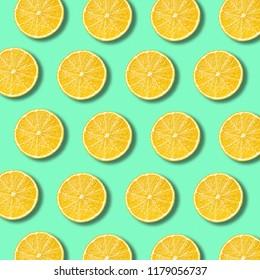 Lemon slices pattern on light vibrant green color background. Minimal flat lay food texture