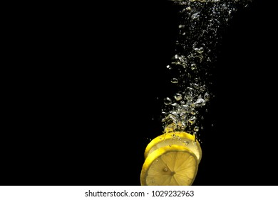 Lemon slices underwater with bubbles of air on a black background