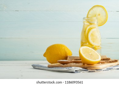Lemon in soda bottle on cutting bord and white table