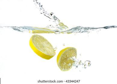 Lemon splashing into water; white background