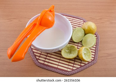 Lemon Squeezer with lemons and juice on wooden background.