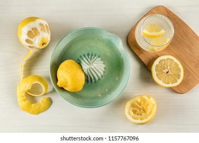 Lemon squeezing directly above Ingredients to prepare fresh lemonade
