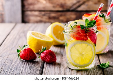 Lemon and strawberry lemonade in glass mason jars on a wooden background. A refreshing summer drink.