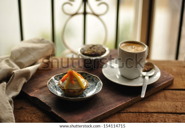 Lemon tart on a plate with coffee on a wooden background