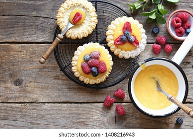 Lemon tartlets with lemon curd and fresh berries. Overhead view