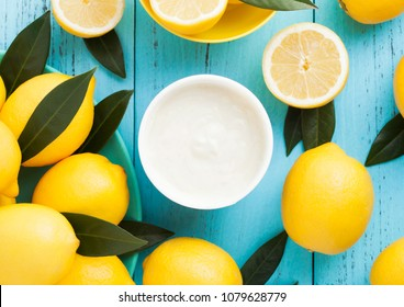 Lemon taste breakfast yoghurt with fresh raw lemons on blue wooden background