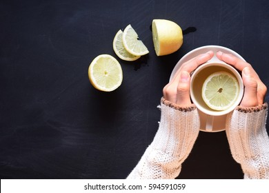 lemon tea with woman wear sweater hands on blackboard background