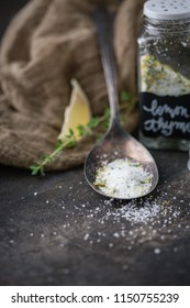Lemon Thyme Herb Salt in Tarnished Spoon on Black Background with Fresh Sprig of Thyme