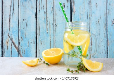 Lemon and thyme infused detox water in a mason jar glass. Summer drink against a rustic blue wood background.