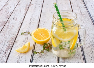 Lemon and thyme infused detox water in a mason jar glass against a rustic white wood background