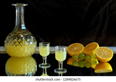 Lemon tincture in a glass carafe and glasses on a black background