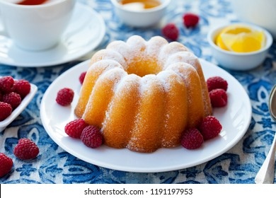 Lemon, vanilla bundt cake with a cup of tea on blue background. Close up.