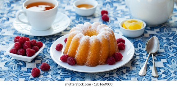 Lemon, vanilla bundt cake with a cup of tea on blue background.