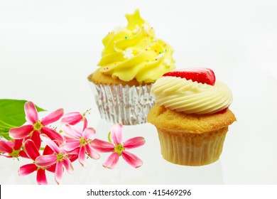 Lemon and Vanilla Cupcakes with pink flowers on white background