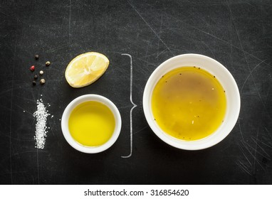 Lemon vinaigrette dressing - recipe ingredients on black chalkboard background from above. Lemon, olive oil, salt and pepper. Layout with free text space.