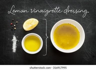 Lemon vinaigrette dressing - recipe ingredients on black chalkboard background from above. Lemon, olive oil, salt and pepper. Kitchen poster layout.