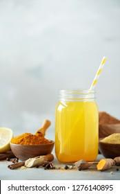 Lemon water with ginger, curcuma, black pepper. Vegan hot drink concept. Ingredients for orange turmeric drink on grey concrete background.