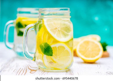 Lemon water, lemonade in mugs with handles, mason jar on a white wooden table. Cut Lemons in the background.