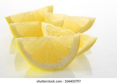 Lemon wedges, backlit on a white plate.