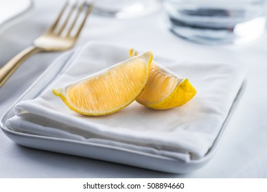 Lemon wedges and a hot wet napkin for cleaning hands after eating seafood