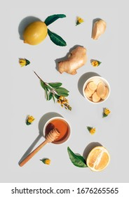 Lemon whole and cut out piece, ginger, honey and yellow flowers pattern on light grey background. Flat lay, top view. Immunity, vitamins, natural health concept