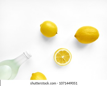 Lemonade in bottle Transparent glass bottle with lemonade, three whole lemons and one lemon's half are lying on white background Photo mockup in top view with copy space