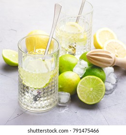 Lemonade With Citrus Lemon and Lime Detox Healthy Water Summer Cold Drink Ice Cubes Wooden Squeezer Glasses Vertical Square Toned
