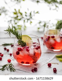lemonade with cranberries, lime and rosemary in a transparent glass