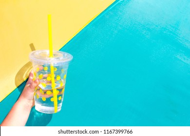 Lemonade drink in a glass on a green and yellow background. Summer concept. Healthy lifestyle.