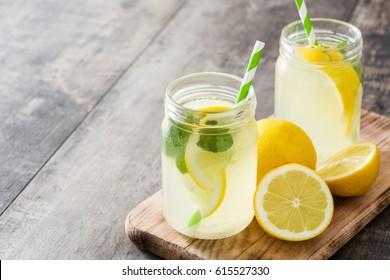 Lemonade drink in a jar glass on wooden background.