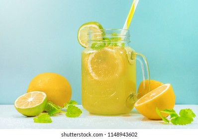 Lemonade drink of soda water, citrus and mint on the light blue background. Cocktail glass with handle and straw, sliced lemon and lime, front view