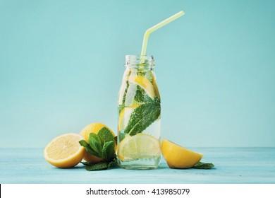 Lemonade drink of soda water, lemon and mint leaves in jar on turquoise background.