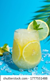 Lemonade frappe with round slice of lemon and mint on blue ice background. Mojito frappe in glass with copy space..