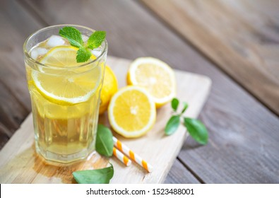 Lemonade with fresh lemon and mint leaves on the wood plank background
