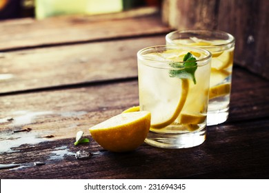 Lemonade with fresh lemon on wooden background